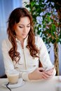 Beautiful girl sits in cafe and reads sms on phone Royalty Free Stock Photo