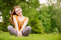 Beautiful girl sits on lawn Royalty Free Stock Photos