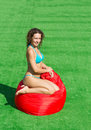 Beautiful girl sits on a soft red pufe the green grass Stock Image