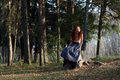 Beautiful girl sits on stump in autumn forest Royalty Free Stock Photo