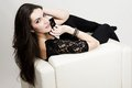 The beautiful girl sitting on armchair in black clothes white Stock Photos