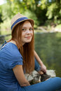 Beautiful girl sitting on the bank of the river Stock Photography