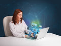 Beautiful girl sitting at desk and watching her photo gallery on young laptop Royalty Free Stock Photo