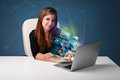 Beautiful girl sitting at desk and watching her photo gallery on young laptop Royalty Free Stock Photos