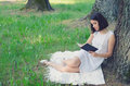 Beautiful girl sitting in forest and reading book in summer Royalty Free Stock Photo