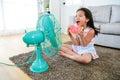 Beautiful girl sitting in front of electric fan