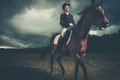 Beautiful girl sitting on a horse outdoors against moody sky Royalty Free Stock Photography