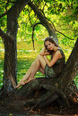 Beautiful girl sitting on a large tree Royalty Free Stock Photos