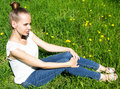 Beautiful girl sitting on the lawn with a dandelion Royalty Free Stock Photo