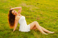 Beautiful girl sitting on the meadow happy elegant woman spring day Royalty Free Stock Photo