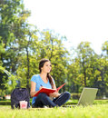 Beautiful girl sitting in park and writing notebook shot with tilt shift lens Royalty Free Stock Image