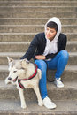 Beautiful girl sitting on stairs with her pet husky dog Royalty Free Stock Photo