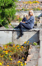 Beautiful girl sitting on a stone wall Stock Images