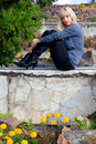 Beautiful girl sitting on a stone wall Royalty Free Stock Photo