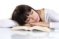Beautiful girl sleeping on a book on white table Royalty Free Stock Photography