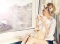 Beautiful girl with small dog on knees a cup og coffee looking through window Stock Photo