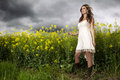 A beautiful girl smiling in a field of yellow flowers brunette smiles and dramatic sky Royalty Free Stock Photo