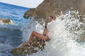 Beautiful girl and splashing wave sitting on a rock on the beach a splashes her back Stock Photos