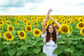 Beautiful girl standing with arms raised in sunflower field Royalty Free Stock Photo