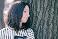 A beautiful girl in a striped T-shirt is standing near tree. Royalty Free Stock Photo