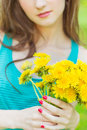 Beautiful girl in a sunny summer day walking in the garden and keeps yellow dandelions in the hands Royalty Free Stock Photo