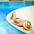 Beautiful girl at swimming pool with hat over head Royalty Free Stock Photo