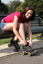 Beautiful girl ties roller skates on park bench Royalty Free Stock Image