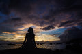 Beautiful girl under clouds a asian at the beach in the after the storm sunset,beautiful harbor and fishing boats located in Stock Images