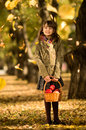 Beautiful girl vertical photo happy little joyful laughter with autumnal leaf in park Royalty Free Stock Image