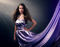 Beautiful girl violet long dress black background Royalty Free Stock Images