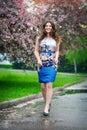 Beautiful girl walks in blooming garden, spring