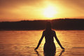 Beautiful girl in water on sunset silhouette Royalty Free Stock Images