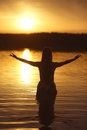 Beautiful girl in water on sunset silhouette Stock Photography