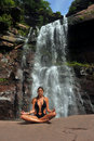 Beautiful girl wearing black one piece swimsuit meditating in lotus yoga pose front of waterfall Royalty Free Stock Image