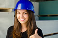 Beautiful girl wearing a blue safety helmet happy worker signing thumbs up construction site background Royalty Free Stock Images