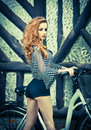 Beautiful girl wearing ultramarine blouse and black shorts in park with bicycle. Pretty red hair woman posing near her bike Royalty Free Stock Photo