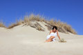 Beautiful girl with white dress posing on the sand hill Stock Photo
