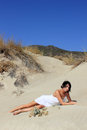Beautiful girl with white dress posing on the sand hill Royalty Free Stock Photo