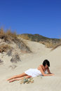 Beautiful girl with white dress posing on the sand hill Royalty Free Stock Image