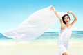 Beautiful girl with white scarf on the beach travel and vacation freedom concept enjoying summer Stock Images