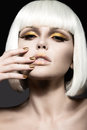Beautiful girl in a white wig with gold makeup and nails celebratory image beauty face picture taken the studio Royalty Free Stock Photo