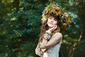 Beautiful girl with wreath on the head of field flowers a she s in woods Stock Photo
