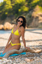 Beautiful girl in yellow bikini attractive brunette posing at the seaside of the greek island evia near a tree trunk wearing Royalty Free Stock Photo