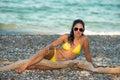 Beautiful girl in yellow bikini attractive brunette posing at the seaside of the greek island evia near a tree trunk wearing Stock Photo