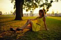 The beautiful girl in a yellow dress sits on a grass in beams of the sunset sun Stock Photos