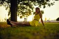 The beautiful girl in a yellow dress sits on a grass in beams of the sunset sun Royalty Free Stock Photography