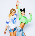 The beautiful girls joined hands and raised them up. Pose in bright summer outfits, jeans. Maiden friendship forever.