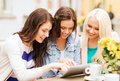 Beautiful girls looking at tablet pc in cafe holidays tourism and internet outside Stock Photos
