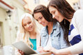 Beautiful girls looking at tablet pc in cafe holidays tourism and internet outside Stock Photo