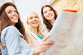 Beautiful girls looking into tourist map in city holidays and tourism concept the Royalty Free Stock Photos